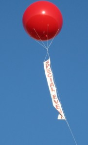 red color helium advertising balloons with vertical banner hanging below it.
